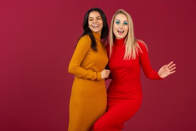 Счастливые улыбающиеся довольно стильные женщины в желтых и красных осенне-зимних модных вязаных платьях позируют изолированно на красной стене