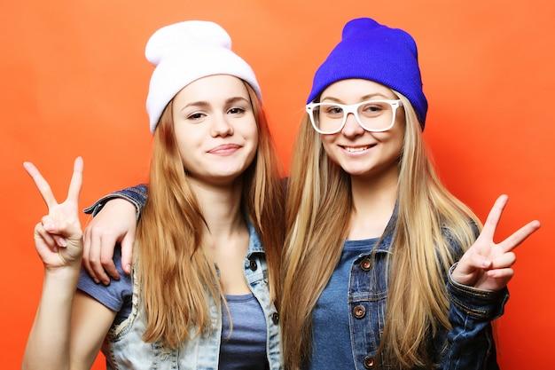 Счастливые улыбающиеся симпатичные девочки-подростки или друзья обнимаются и показывают