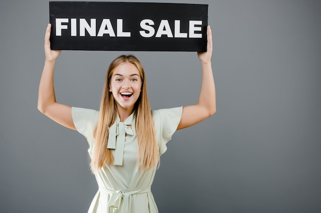 Happy smiling pretty woman with final sale sign isolated over grey