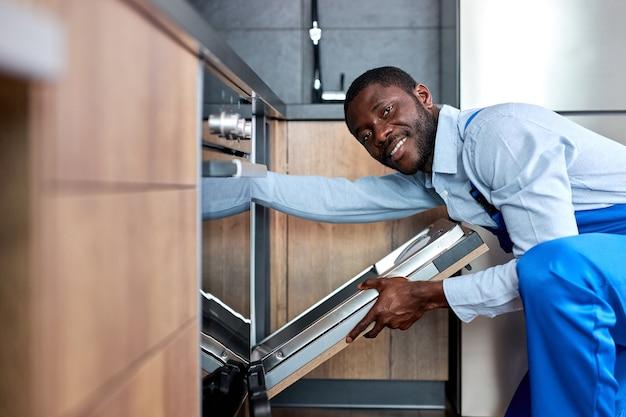 青いオーバーオールの制服を着た幸せな笑顔のプロのアフリカ系アメリカ人の便利屋が食器洗い機を修理しようとしています、自信を持って請負業者が修理前にそれを調べて、側面図の肖像画、カメラを見てください
