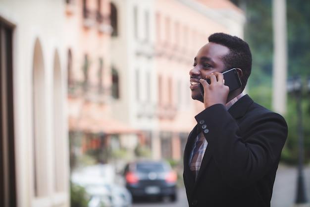 スマートフォンを使用して幸せな笑顔のプロのアフリカ人。携帯スマートフォンを持って話しているビジネスマン