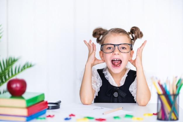 Счастливый улыбающийся ученик за столом. ребенок в классе с карандашами, книгами. малыш девочка из начальной школы.
