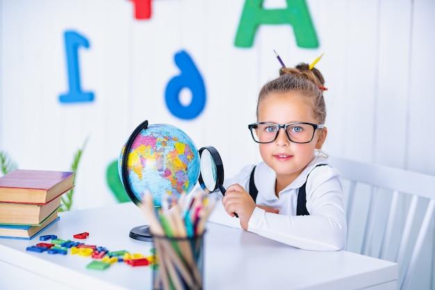 책상에서 행복 하 게 웃는 눈동자. 연필, 책 교실에서 아이. 초등학교에서 꼬마 소녀.
