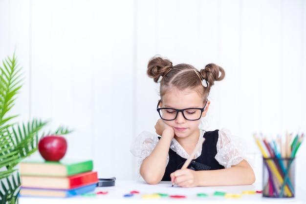Счастливый улыбающийся ученик за столом. девушка в классе с карандашами, книгами. малыш девочка из начальной школы.