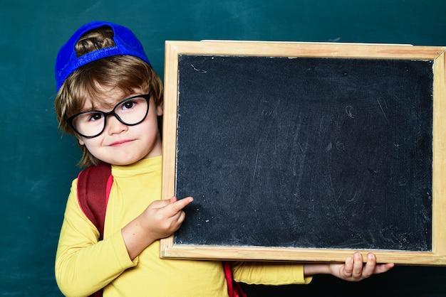 幸せな笑顔の生徒が机に向かって描いています。黒板で元気な笑顔の子。教室