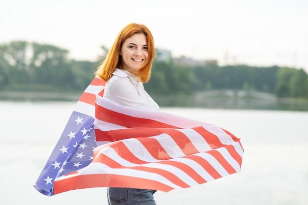 그녀의 어깨에 미국 국기와 함께 행복 하 게 웃는 빨간 머리 소녀