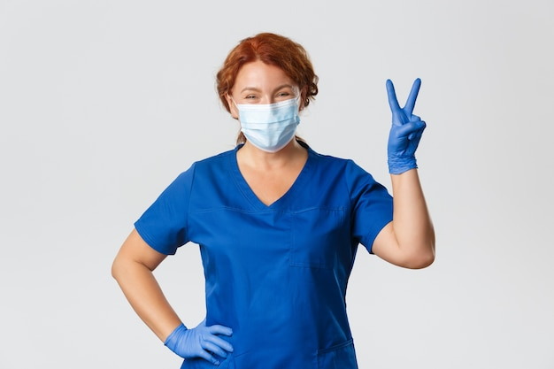 Счастливая улыбающаяся рыжая женщина-врач, медсестра, оставаясь позитивной, в медицинской маске и перчатках в клинике, работая с пациентами, показывают знак мира.