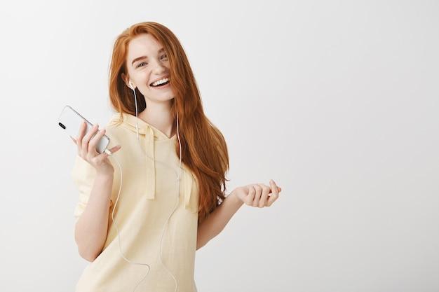 イヤホンで音楽を聴くと携帯電話を保持している幸せな笑顔赤毛の女の子