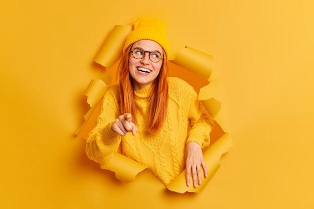 Счастливый улыбающийся рыжий женщина указывает на, носит свитер шляпы и очки.