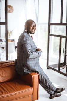 幸せな笑顔の金持ちのアフリカ系アメリカ人実業家の成功したメディア王は、スタイリッシュで高価なスーツを着ています...