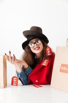 종이 쇼핑백 함께 앉아 행복 한 미소 판매 여자