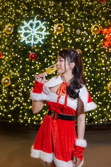Happy smiling santa girl is cute in red suit and hand holding champagne