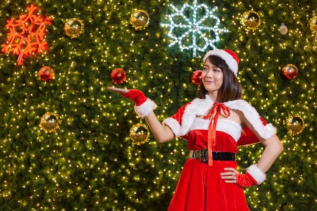Happy smiling santa girl is cute in red suit with christmas tree background celebration