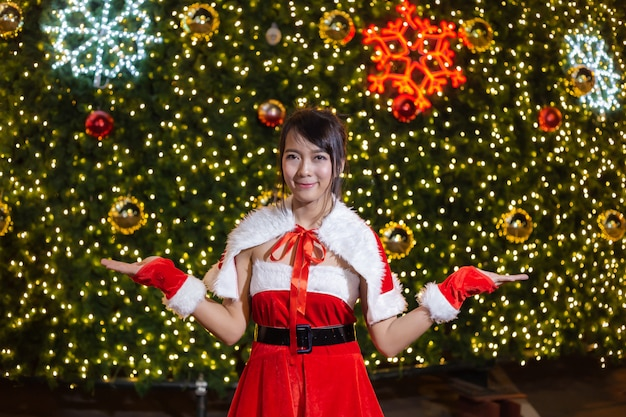 Happy smiling santa girl is cute in red suit with christmas tree background