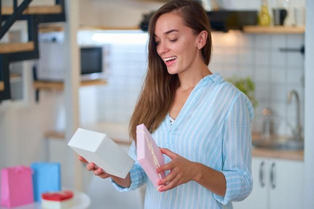 Счастливая улыбающаяся довольная довольная милая любимая удивленная женщина получила подарочную коробку на женский день на 8 марта