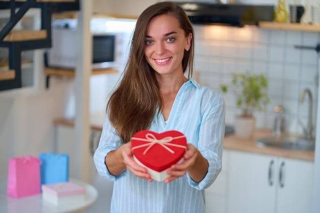Счастливая улыбающаяся довольная милая любимая женщина держит подарочную коробку в форме сердца на день святого валентина 14 февраля