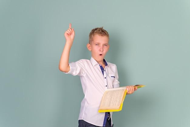 幸せな笑顔の男子生徒が左を指して学校の販売に戻る黒板に対して制服を着た子供