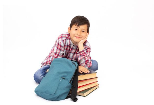 学校に戻って白い表面で隔離、床に座って幸せな笑顔の男子生徒