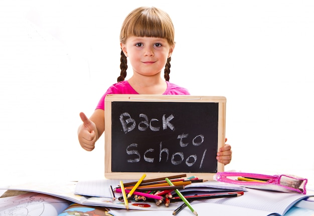 Happy smiling schoolchild holding small blackboard with text