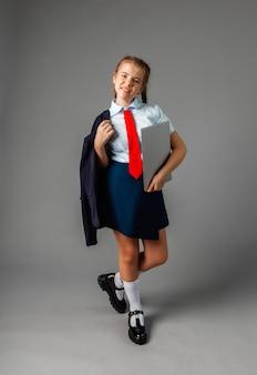 幸せな笑顔の女子高生12歳、ラップトップを保持し、灰色の背景で隔離、カメラを見てください。
