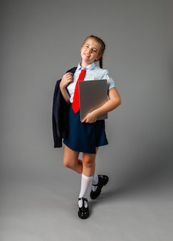 Happy smiling schoolgirl 12 years old, holding a laptop, isolated on gray background, looking at camera.