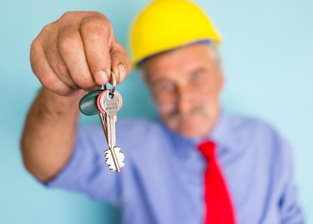 Счастливый улыбающийся старший архитектор, держащий ключи для готового нового дома