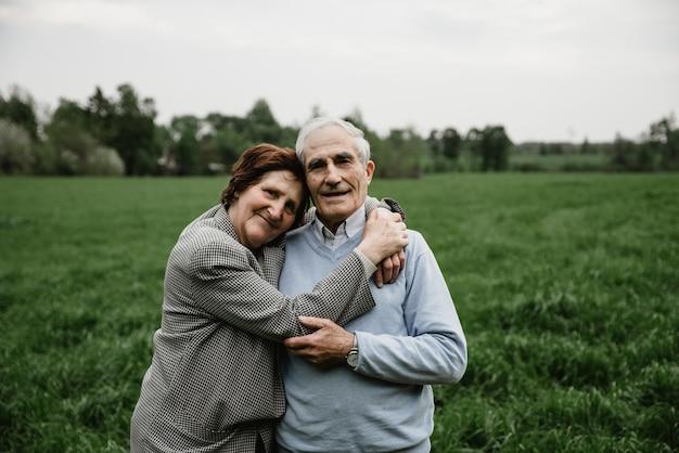 Счастливый улыбающийся старший пара в любви на природе, весело. пожилая пара на зеленом поле. милая пара старших гулять и обниматься в весеннем лесу