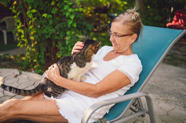 Счастливый улыбающийся старший пожилая женщина в очках расслабляющий в летнем саду на открытом воздухе, обнимая домашнего полосатого кота. пенсионеры пожилых людей и животных концепция домашних животных