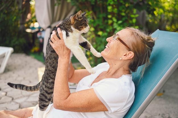 国内のぶち猫を抱いて屋外の夏の庭でリラックスしたメガネで幸せな笑顔の年配の女性。引退した老人と動物のペットの概念