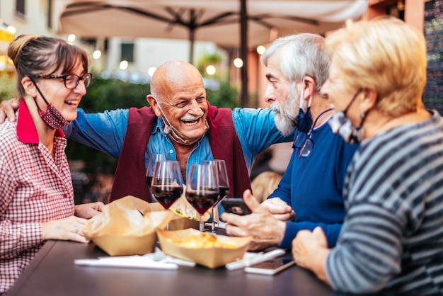Happy smiling senior people drinking wine at bar restaurant outside - new normal life concept with happy people having fun together with open face mask
