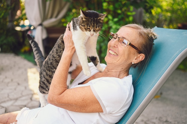 Happy smiling senior woman in glasses relaxing in summer garden outdoors, hugging domestic tabby cat