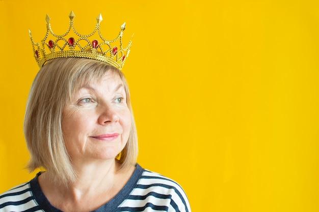 彼女の頭にかわいい王冠と黄色の背景に幸せな笑顔の年配の女性。年功序列、かわい子ちゃんの祖母、年金についての喜びの老後の概念。アンチエイジ