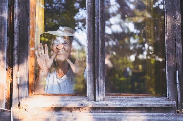古い木造の村の家でポーズをとって幸せな笑顔の年配の女性