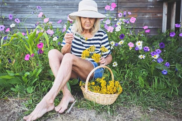 花と夏の庭でポーズをとって幸せな笑顔の年配の女性