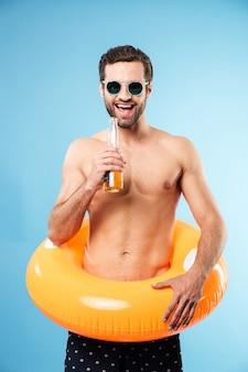 インフレータブルリングを着て幸せな笑みを浮かべて上半身裸の男