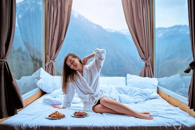 Счастливая улыбающаяся сонная просыпающаяся женщина со стройными длинными ногами в халате тянется в белой кровати в гостиничном номере с большими окнами во время утреннего завтрака. начало нового дня