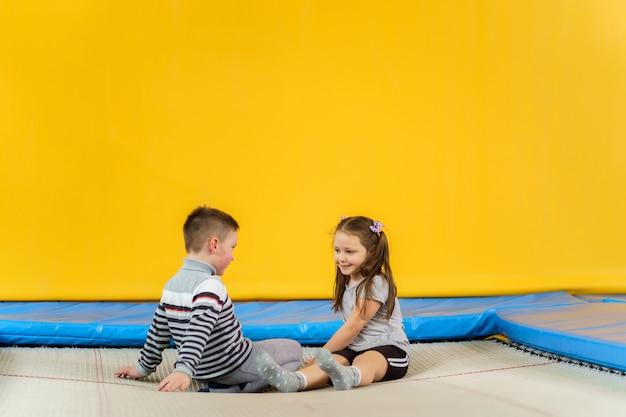 Счастливые улыбающиеся маленькие дети сидят на батуте в помещении и играют в развлекательном центре
