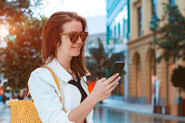 세련된 선글라스를 끼고 웃고 있는 행복한 여학생 여학생은 여름날 스마트폰으로 밖에 나간다