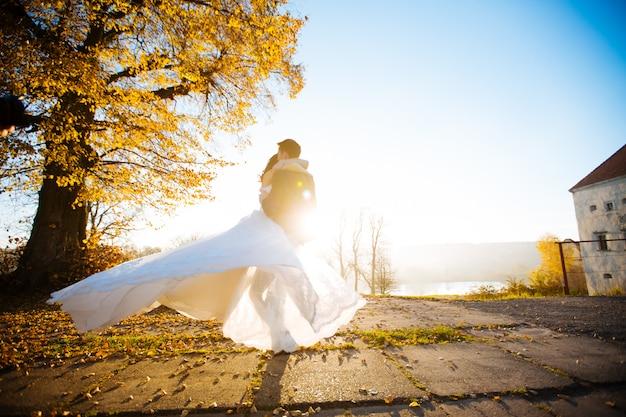 행복 한 미소 세련 된 신부와 신랑 꽃의 부케와 함께 여름 녹색 공원에서 산책, 춤과 그들의 결혼 날에 재미