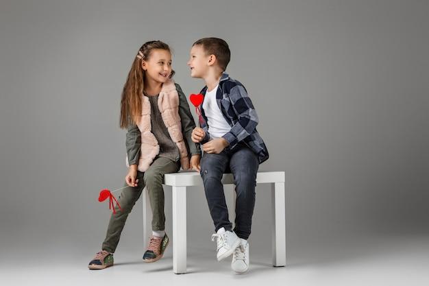 Счастливая улыбающаяся стильная маленькая пара, ребенок, девочка и мальчик с красными сердцами на палочке в модной одежде, сидя вместе