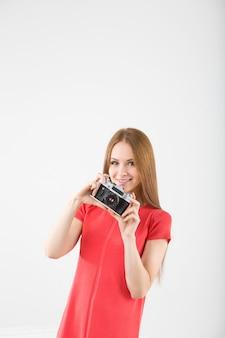 ビンテージカメラで幸せな笑顔のスタイリッシュなティーンエイジャー