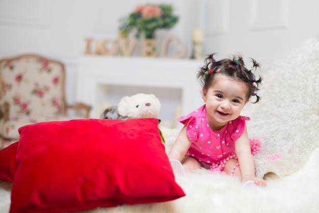 Happy smiling sweet baby girl sitting on sofa with bear toy