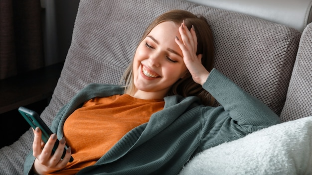Счастливая улыбающаяся девочка-подросток смеется, текстовые сообщения по телефону, серфинг в интернете или чате, используя смартфон, лежа на диване. молодая женщина использует смартфон для развлечения на досуге, смеется.
