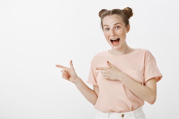 Adolescente sorridente felice che posa contro il muro bianco