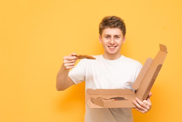 Счастливый улыбающийся подросток держит в руках коробку и кусок пиццы