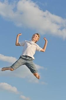 하늘을 배경으로 점프하는 행복한 미소 십대