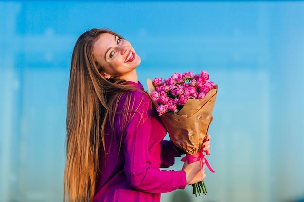 長い髪の幸せな笑顔のティーンエイジャーは、クラフト紙で茂みのバラの束を受け取りました