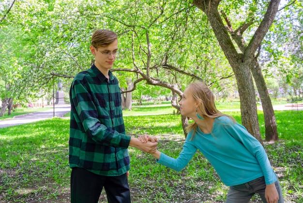 Счастливые улыбающиеся подростки, брат и сестра, играя в парке