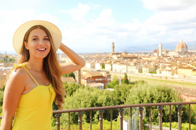 Счастливая улыбающаяся туристическая девушка во флоренции, италия. портрет молодой женщины, посещающей регион тоскана в италии.