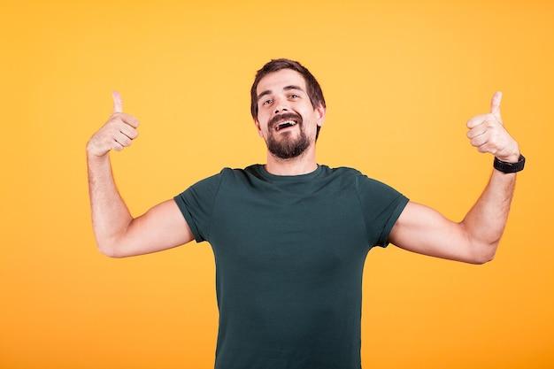 黄色の背景に親指を表示して幸せな笑顔のトレンディな男。かっこいい男が彼の承認を与える